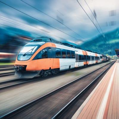 Ein schneller Zug fährt durch einen Bahnhof