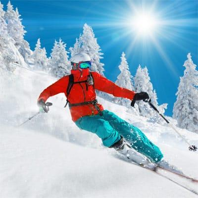 Ein Skifahrer im Pulverschnee bei Sonnenschein