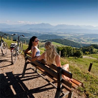 Zwei junge Damen auf einer Bank blicken ins Tal